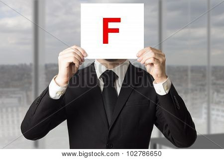 Businessman In Suit Holding Up Sign With Letter F