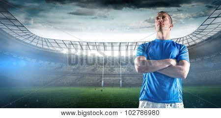Serious rugby player looking away with arms crossed against rugby stadium