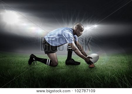 Rugby player keeping ball on kicking tee against rugby stadium