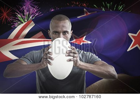 Portrait of sportsman pressing rugby ball against fireworks exploding over football stadium