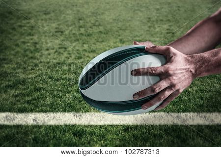Cropped image of sports player holding ball against rugby pitch