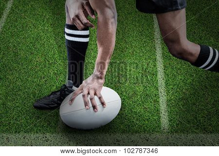 Low section of sportsman holding rugby ball against pitch with lines