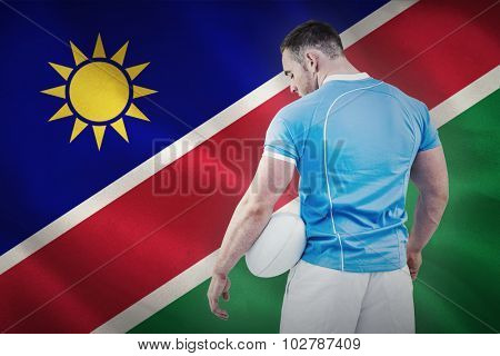 Rugby player standing with ball against namibian flag on white background
