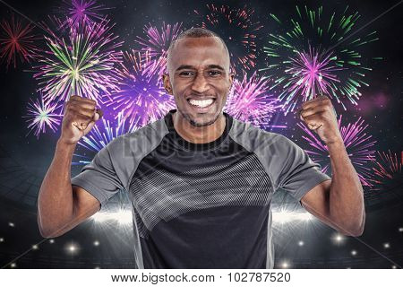 Portrait of rugby player cheering after success in game against fireworks exploding over football stadium