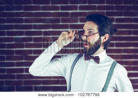 Shocked hipster holding eyeglases against brick wall