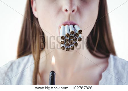 Woman lighting many cigarettes in mouth on white background