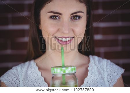 Pretty woman sipping on green juice on red brick background