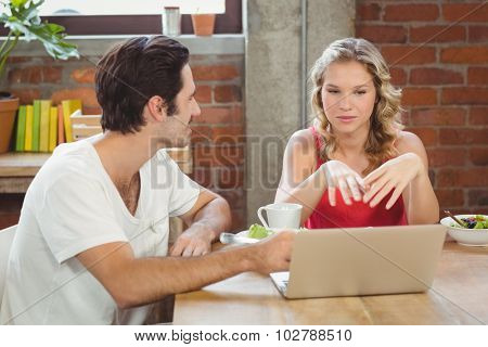 Businesswoman briefing colleague during coffee break in creative office
