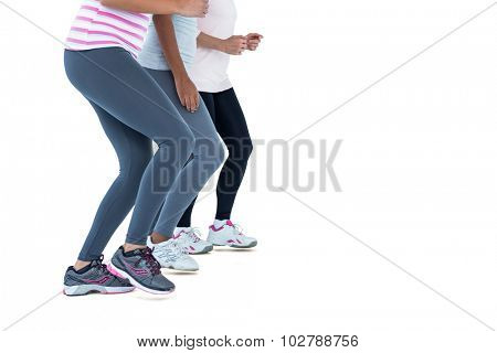Low section of female friends jogging against white background