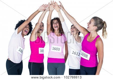 Smiling athletes putting their hands together with arms raised while standing against white background