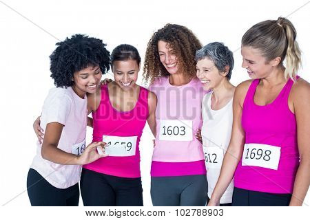 Smiling female athletes using smartphone with arms around while standing against white background