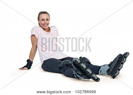 Portrait of happy female inline skater relaxing over white background