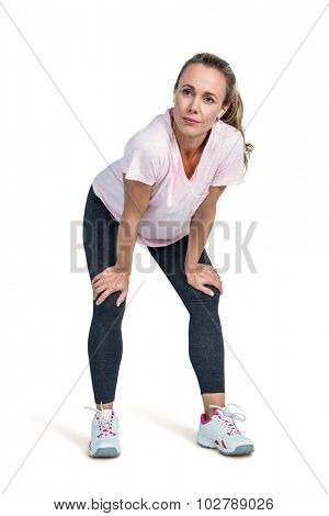 Thoughtful sporty woman bending against white background