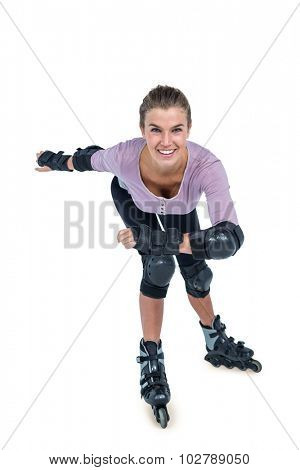 Portrait of happy young woman inline skating over white background
