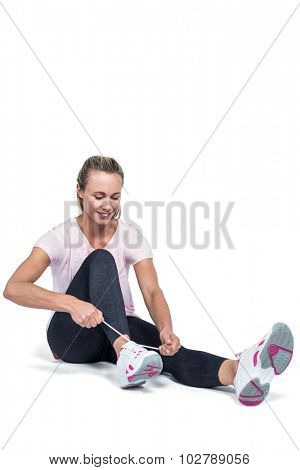 Fit woman smiling while tying shoelace against white background
