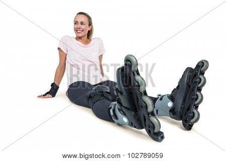 Cheerful female inline skater relaxing over white background
