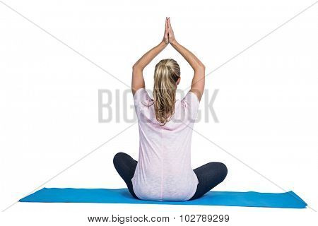 Rear view of fit woman in yoga position sitting on exercise mat against white background