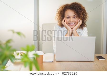 Portrait of smiling businesswoman with hand on chin sitting by laptop on desk in office