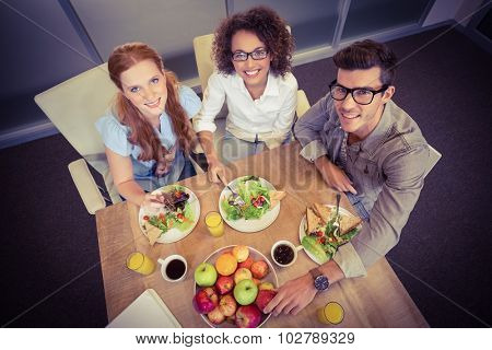 Portrait of smiling business people having brunch in creative office