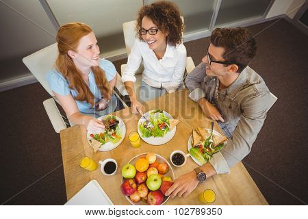 High angle view of happy business people enjoying brunch in creative office