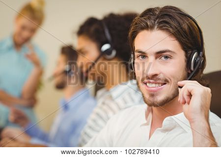 Portrait of male employee working in call center with coworkers
