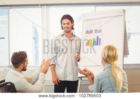 Business people clapping for male colleague for his successful presentation in creative office