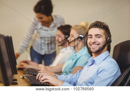 Portrait of male employee with coworkers working in call center