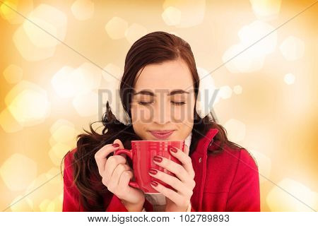Woman in winter clothes enjoying a hot drink eyes closed against yellow abstract light spot design