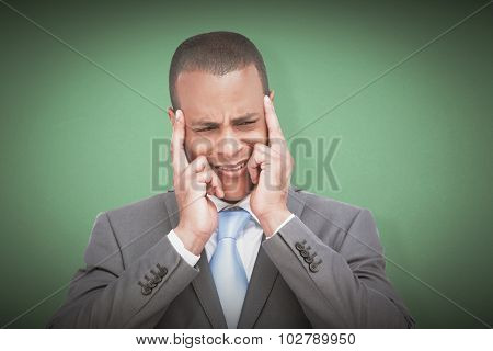 Stressed businessman putting his fingers on his temples against green