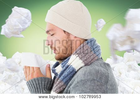 Handsome man in winter fashion blowing his nose against green vignette