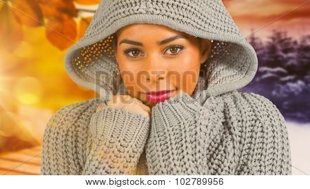 Pretty girl in winter jumper looking at camera against autumn changing to winter