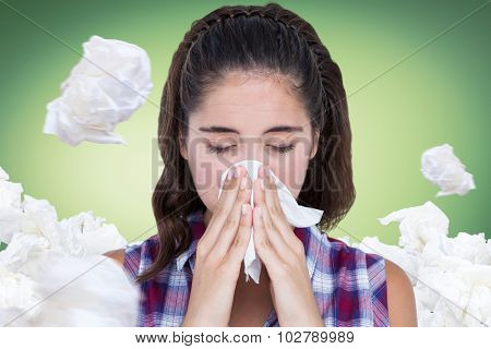 Close-up of sick woman sneezing in a tissue against green vignette
