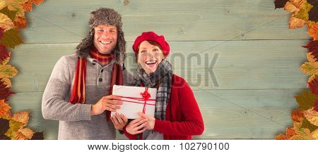 Couple smiling and holding gift against bleached wooden planks background