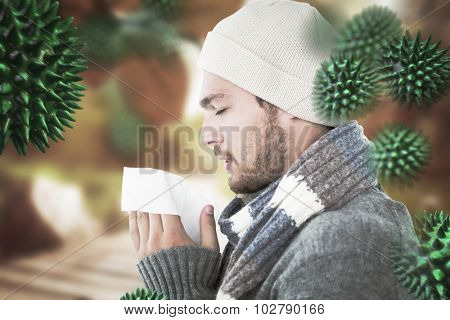 Handsome man in winter fashion blowing his nose against autumn scene