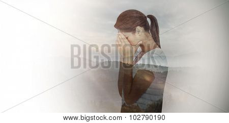 Side view of upset woman covering face against trees and mountain range against cloudy sky