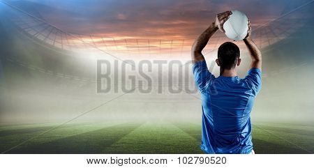 Rear view of rugby player throwing ball against rugby pitch