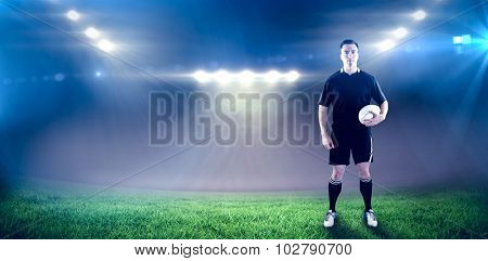 Rugby player holding a rugby ball against rugby stadium