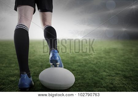 Rugby player posing feet on the ball against spotlights