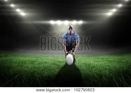 Portrait of rugby player holding ball while kneeling against rugby stadium