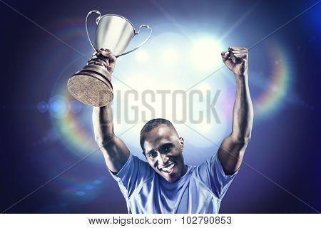 Portrait of happy sportsman cheering while holding trophy against spotlights
