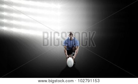 Portrait of rugby player holding ball while kneeling against spotlight