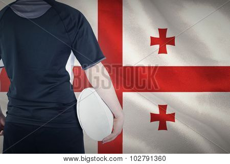 Back turned rugby player holding a ball against georgian flag with red cross symbols