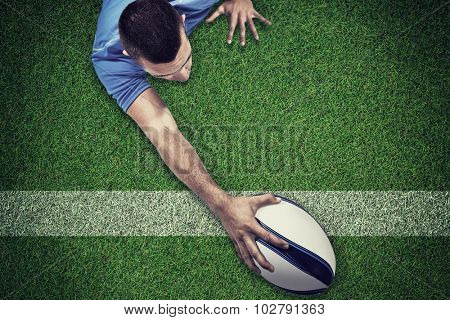 Rear view of rugby player lying in front with ball against pitch with line