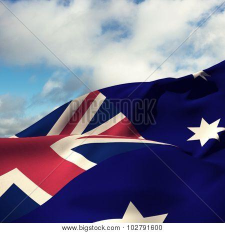 Australian flag against blue sky with clouds