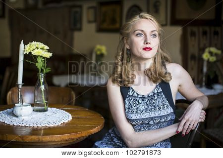 Portrait of young beautiful woman in a vintage cafeteria.