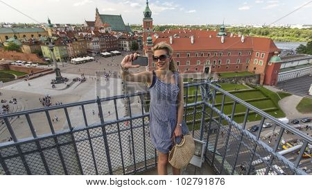 Beautiful blond woman making selfie with phone on the background Warsaw Castle Square.