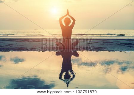 Female silhouette in yoga with reflection in water, meditation pose at amazing sunset.