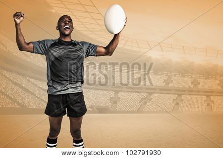 Cheerful sportsman with clenched fist holding rugby ball against orange vignette