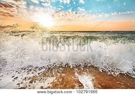 Beautiful Sunrise At The Sea With Shorebreak Splashes On Sandy Beach.