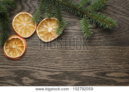 spruce twig with dried orange slices on oak table, christmas